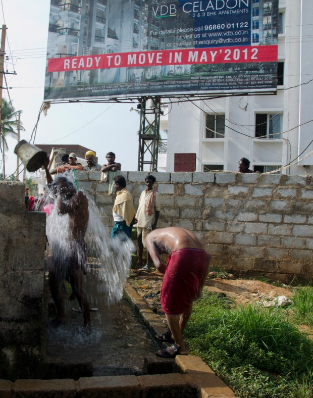Construction workers taking a bucket bath in front of a billboard marketing a middle-class gated community in Bangalore - by SabinavonKessel - wikimedia commons
