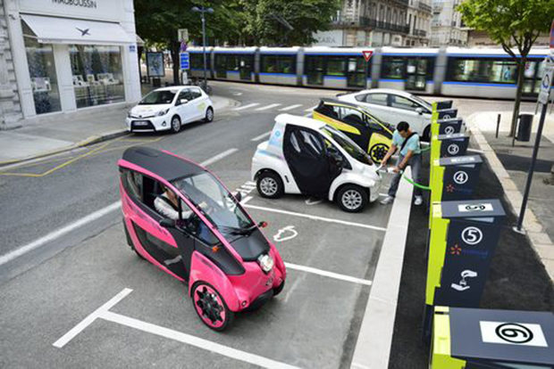 "Toyota i-ROAD and COMS at a charging station for ""Cité lib by Ha-mo"" EV sharing trial. Click to enlarge"