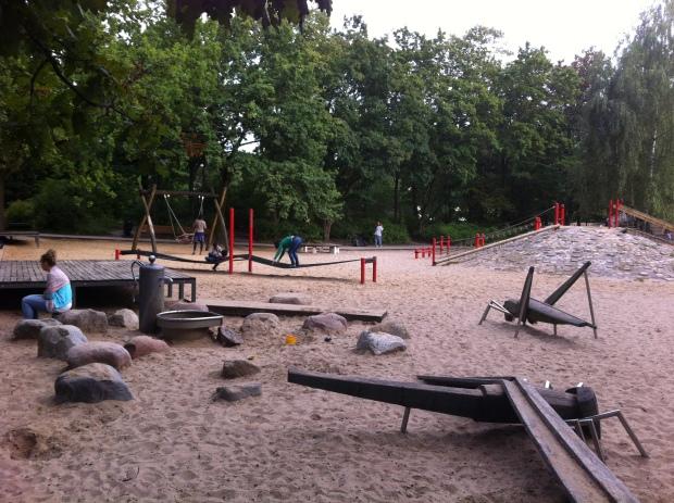 El parque entre Löhmuhlenstrasse y Landwehrkanal en Treptow tiene una zona de niños con fuente para jugar, piedras, arena, insectos gigantes, trampolín y un montículo de adoquines con juegos para trepar.